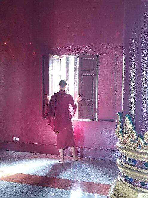 monk opening window Wat Rajamontean Chiang Mai